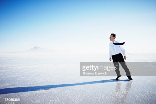 Scientist leaning into wind on salt flats : Stock Photo