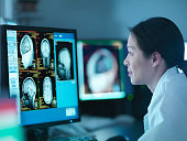 Scientist looking at 3D rendered graphic scans from Magnetic Resonance Imaging (MRI) scanner, close up