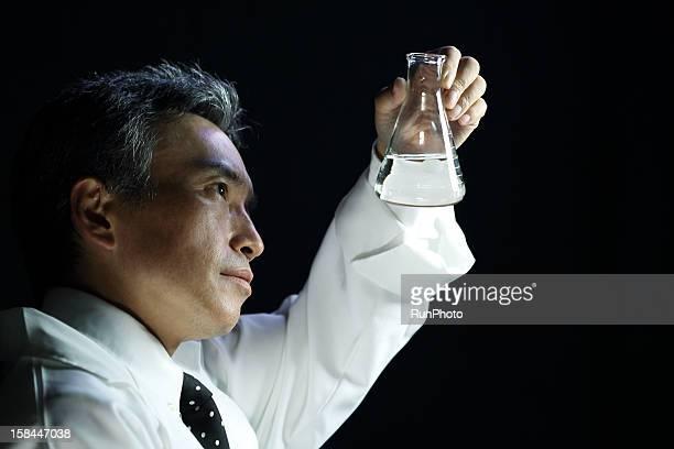 scientist looking at flask