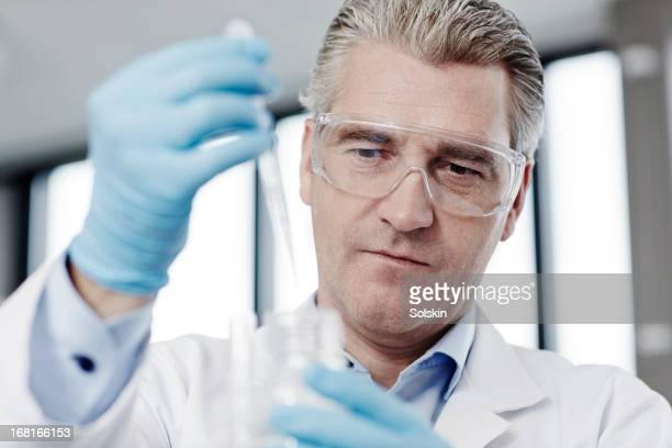 Scientist looking at laboratory pipette sample
