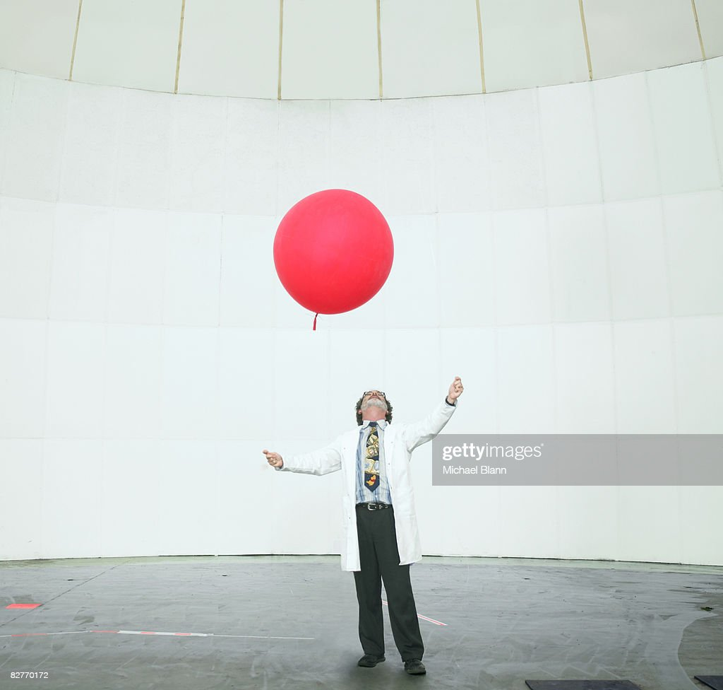 Scientist looking up at weather balloon : Stock Photo
