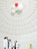 scientist looking upwards at balloons