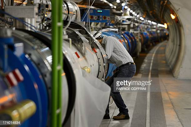 A scientist looks at a section of the CERN's Large Hadron Collider tunnel during maintenance works on July 19 2013 in Meyrin near Geneva Tests at the...
