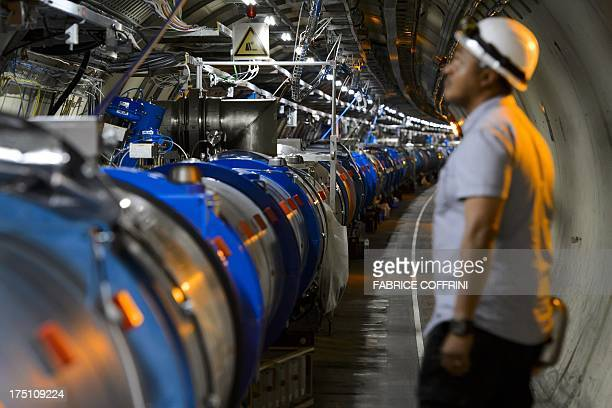 A scientist looks at a section of the European Organisation for Nuclear Research Large Hadron Collider during maintenance works on July 19 2013 in...