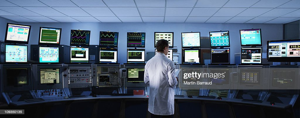 Scientist monitoring computers in control room : Stock Photo