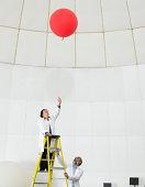 Scientist on ladder watches balloon float away