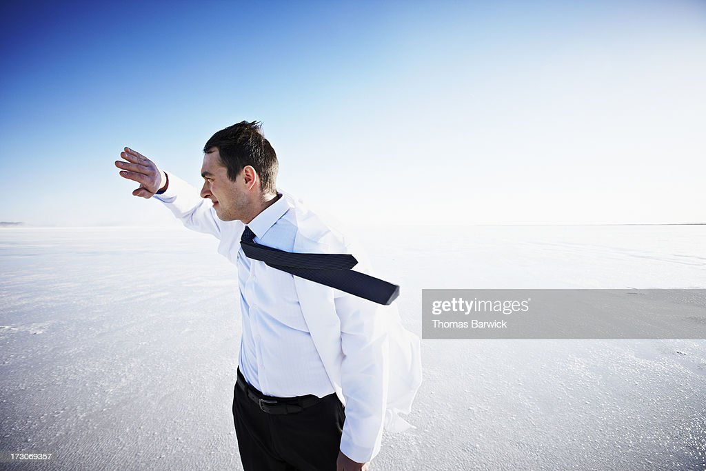 Scientist on windy salt flat hand in front of face : Stock Photo