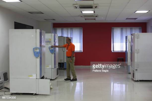 A scientist opens a large refrigerator that stores the microbial collection A mega repository of living organisms in India a kind of a Noahs Ark and...