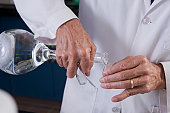 Scientist pouring liquid from a flask to a vial in the laboratory of water treatment plant