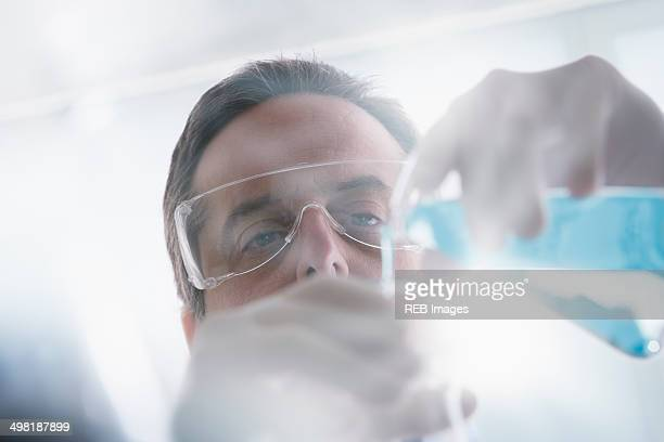 Scientist pouring liquid into test tube