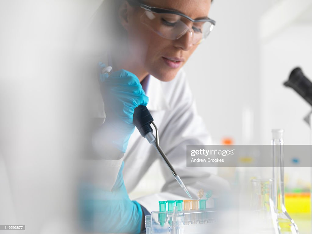 Scientist putting liquid into tubes : Stock Photo