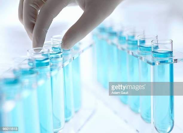 Scientist reaching for test tube