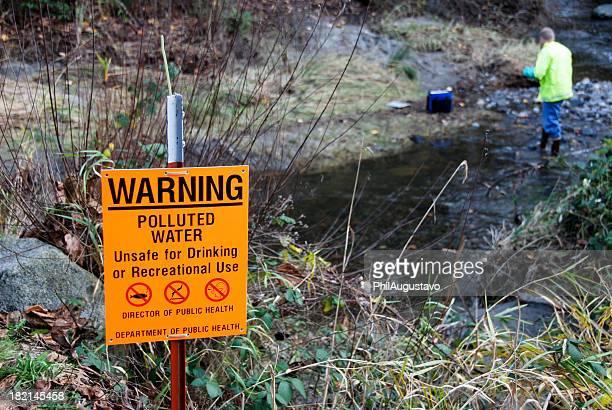 Scienziato campionamento dei livelli di inquinamento in creek