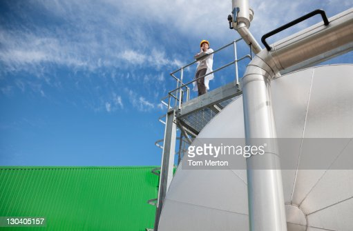Scientist standing on walkway on tanks : Stock Photo