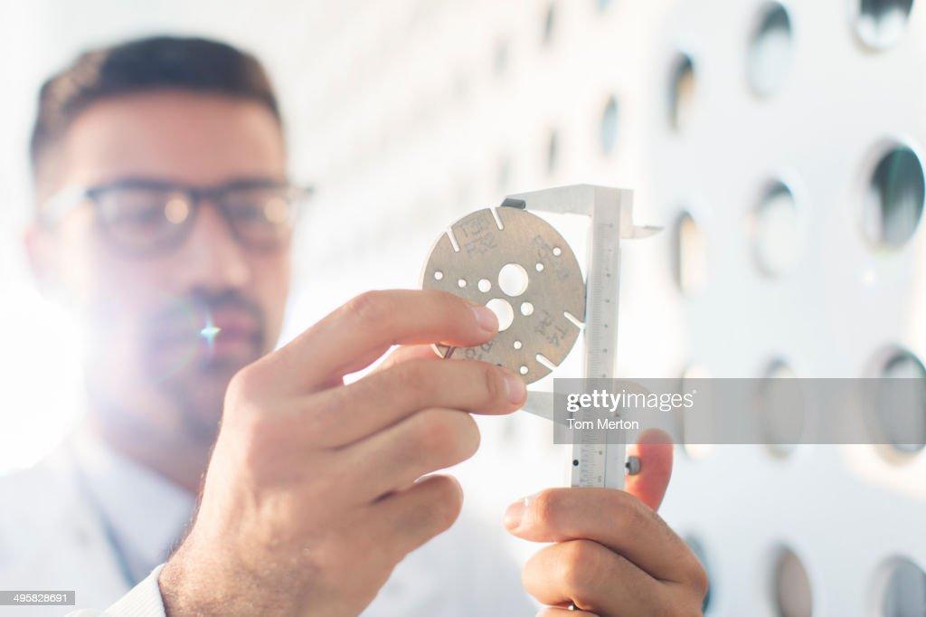 Scientist using calipers