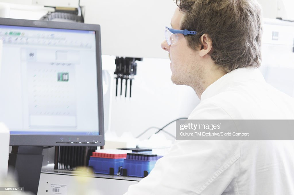 Scientist using computer in lab : Stock Photo