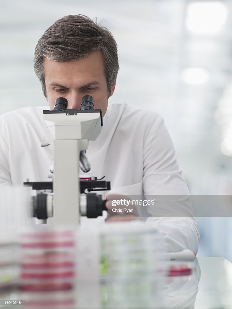 Scientist using microscope in lab : Stock Photo