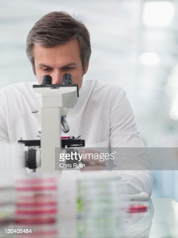 Scientist using microscope in lab : Stock Photo