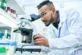 Side view portrait of young Middle-Eastern scientist looking in microscope while working on medical research in modern laboratory