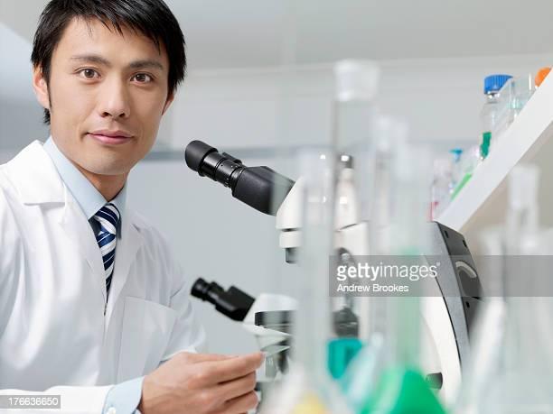 Scientist using microscope in laboratory, portrait