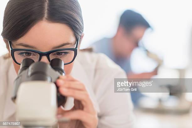 Scientist using microscope in research laboratory