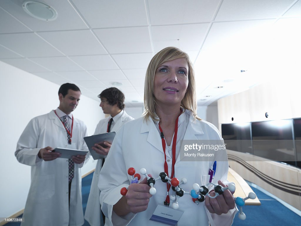 Scientist using molecular model in lab : Stock Photo
