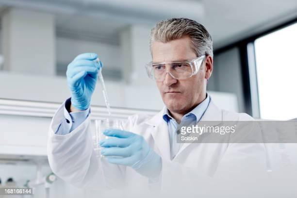Scientist using pipette in laboratory