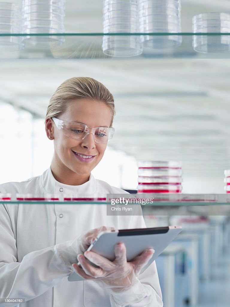 Scientist using tablet computer in lab : Stock Photo