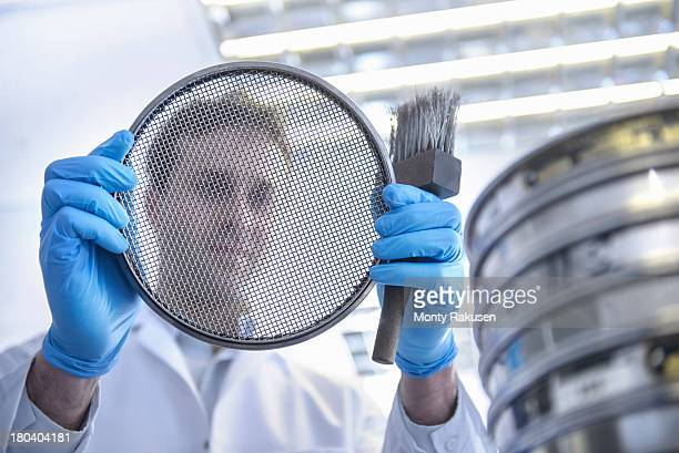 Scientist viewed through mesh component he is holding in laboratory