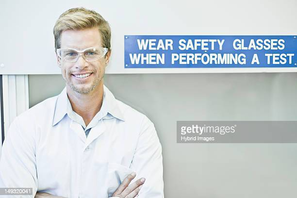 Scientist wearing goggles by safety sign