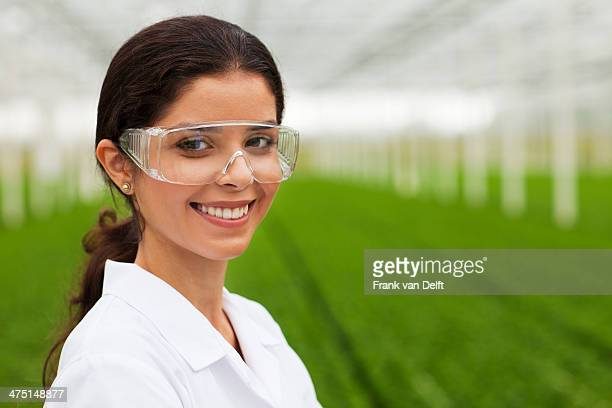 Scientist wearing goggles in front of plants in greenhouse