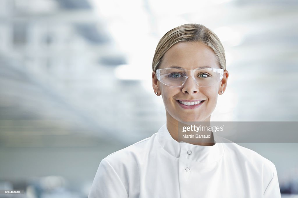 Scientist wearing protective glasses in lab : Stock Photo