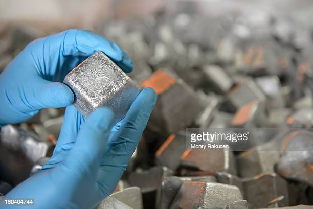 Scientist wearing surgical gloves holding piece of aluminium scrap in aluminium recycling plant, close up