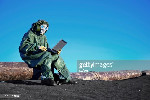 Scientist with a laptop on chemically contaminated area : Stock Photo