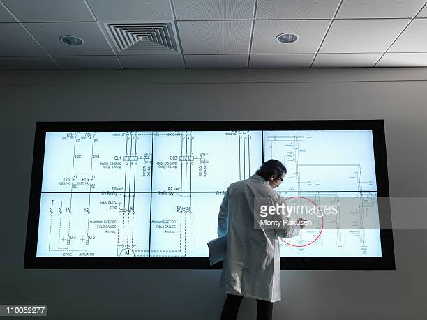 Scientist with diagrams on screen