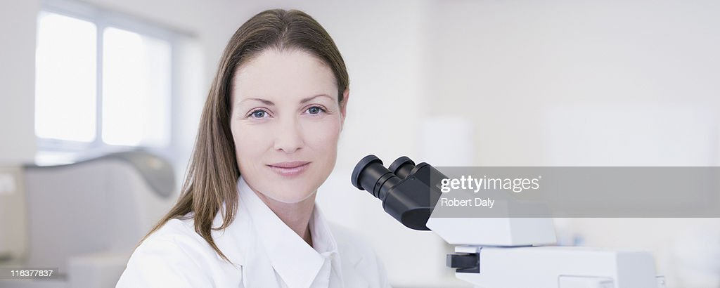 Scientist with microscope in laboratory : Stock Photo