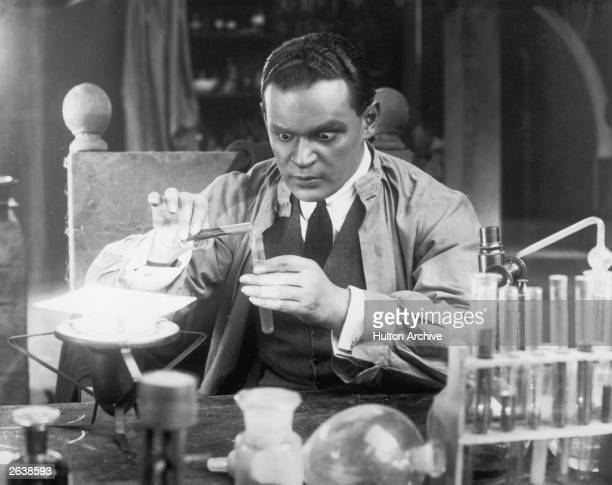 A scientist with staring eyes pours liquid from one test tube to another in a laboratory scene from an unknown German film