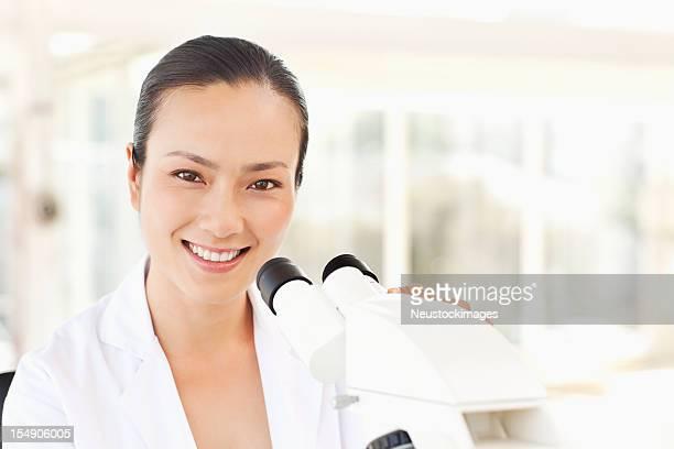 科学者が、顕微鏡付き