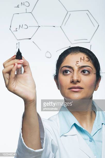 Scientist writing chemical formula
