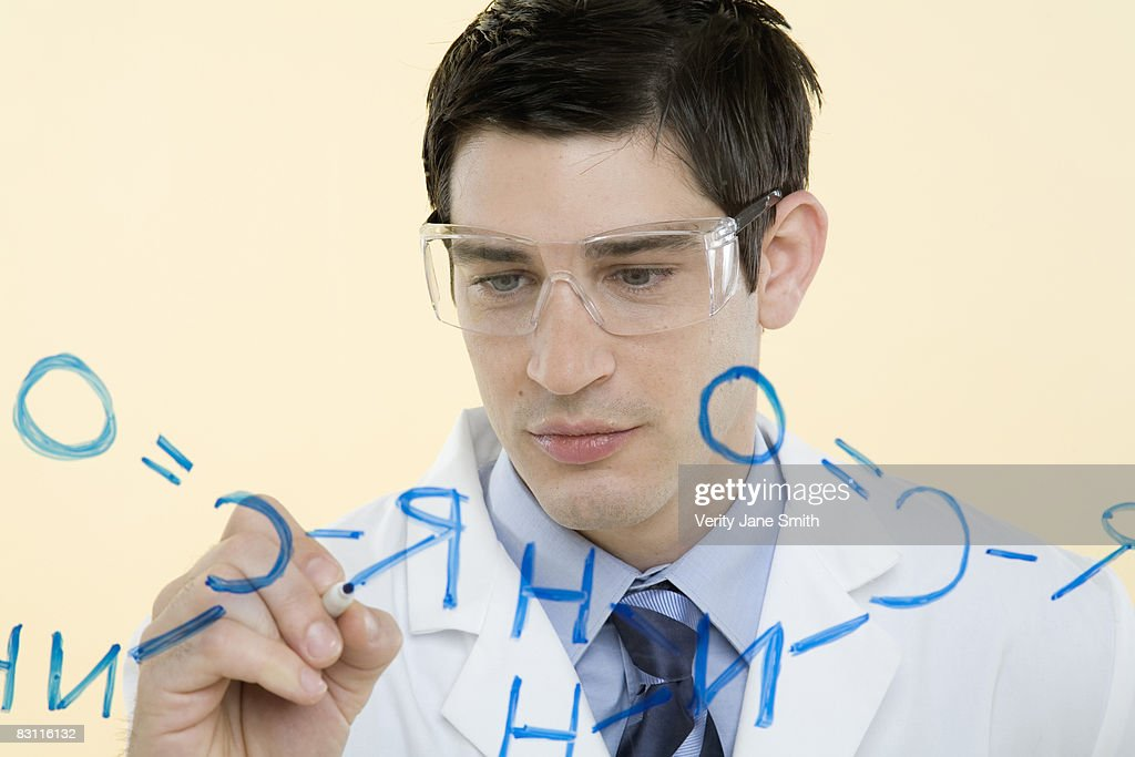 Scientist writing chemical formula : Stock Photo
