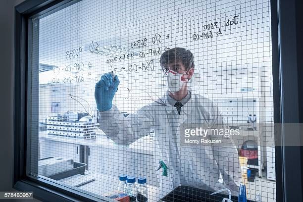 Scientist writing formulae on window of laboratory in graphene processing factory