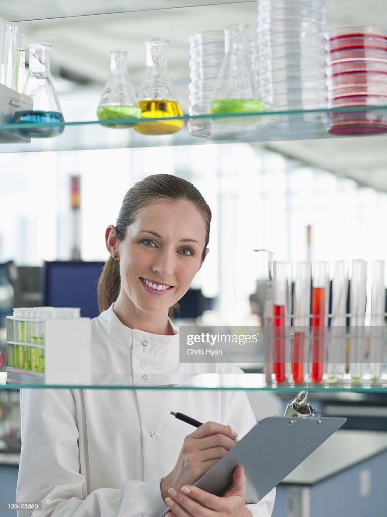 Scientist writing on clipboard in lab : Stock Photo
