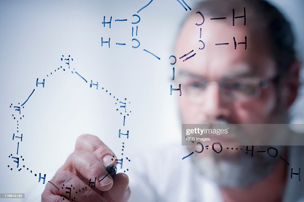 Scientist writing scientific symbols on glass