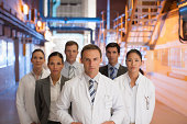 Scientists and business people standing together in factory