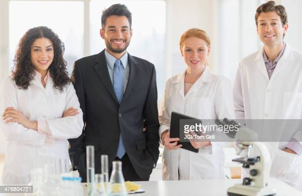 Scientists and businessman smiling in laboratory