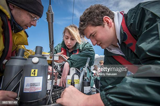 Scientists assembling sea water sampling experiment on research ship
