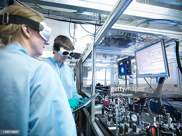 Scientists by monitors with laser beam profiles and LabView code