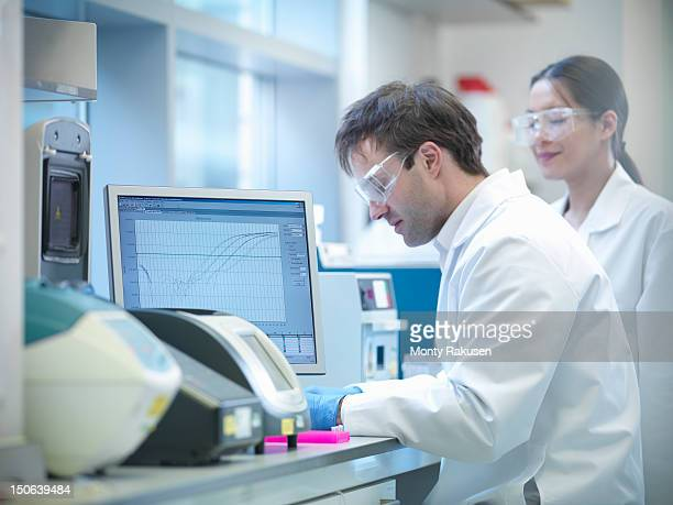 Scientists conducting the process of Polymerase chain reaction (PCR) to amplify DNA by using a thermocycler to create samples