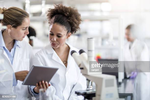 Scientists Discussing and Using Digital Tablet
