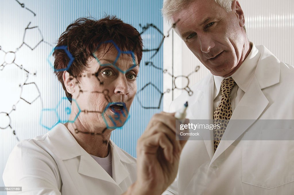 Scientists drawing chemical diagram on glass : Stock Photo
